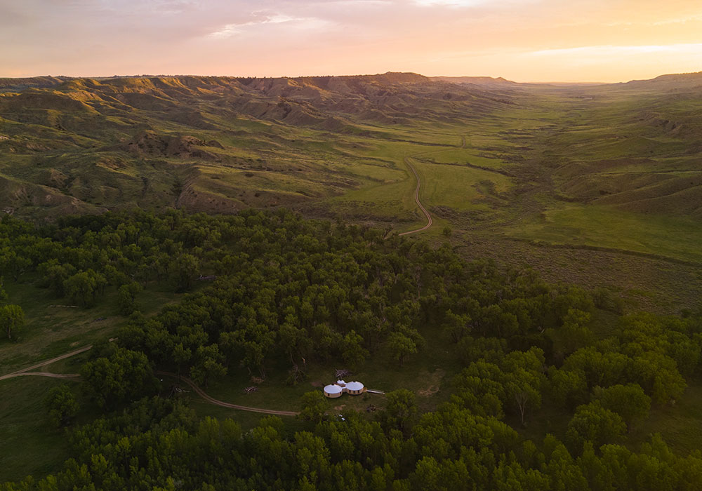 Drone photo of the Craighead Hut with cottonwoods and green hills.